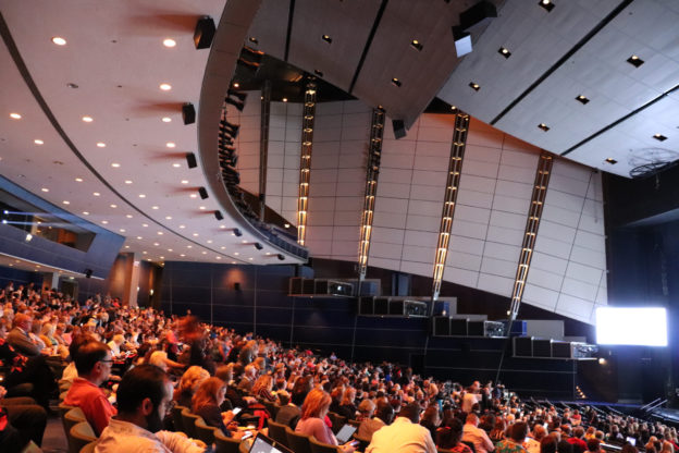 Auditorium filled with people in front of a stage