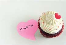 Cupcake with a heart shaped paper that reads thank you beside it