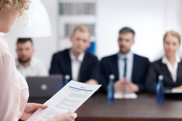Woman holding resume with men and woman sitting at table in background blurred out