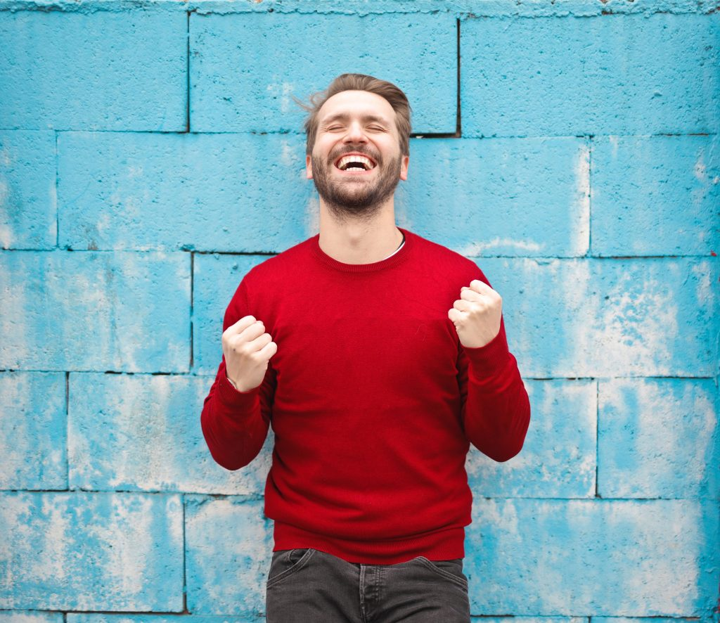 Man standing against a blue brick wall smiling