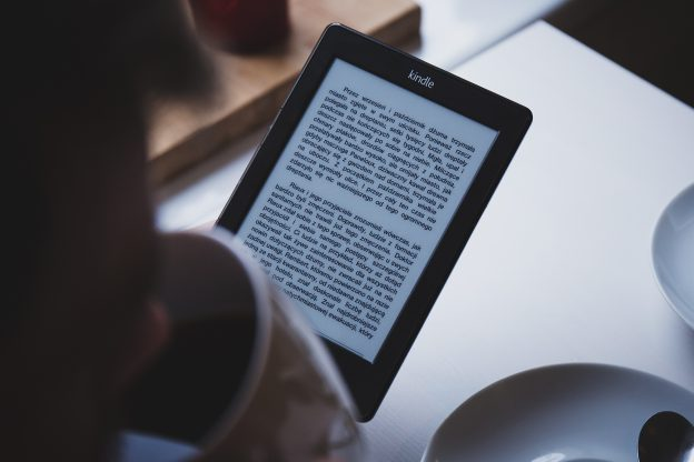 Person reading a book on a tablet taking a sip of coffee