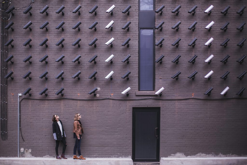 two women standing under different coloured security cameras