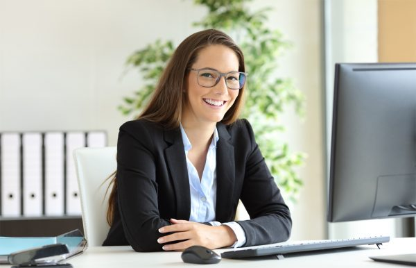 Woman sitting at a desk smiling while looking at the camera