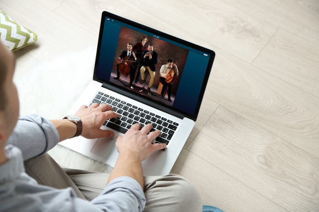 Man watching musical performance online on laptop. Video call and chat concept.