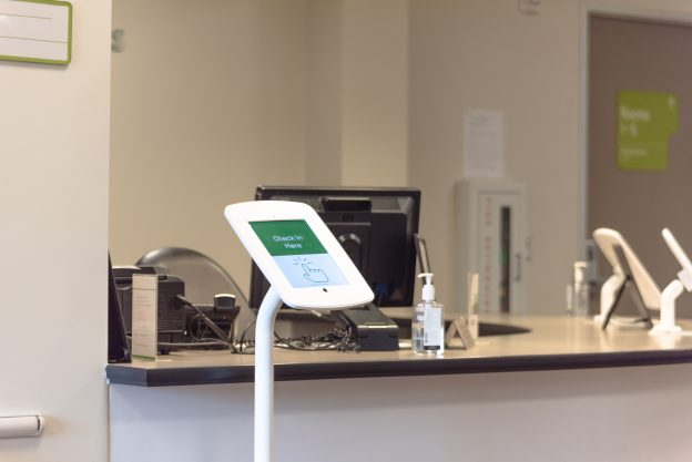 Check-in kiosk tablet upon arrival at front desk of test center for diagnostic testing, medical.