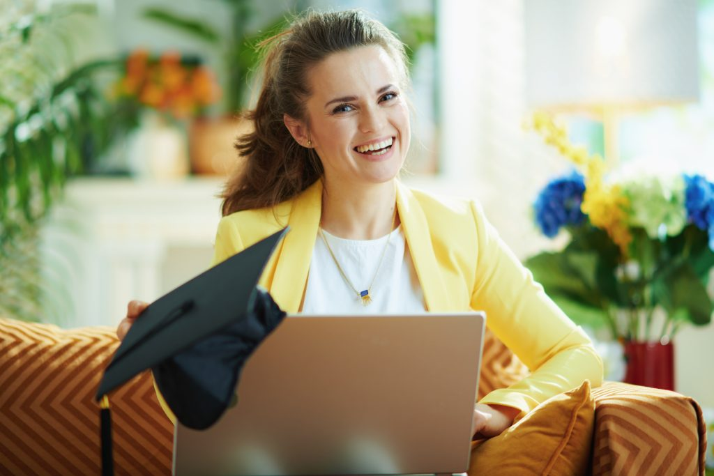 happy young woman with graduation cap and laptop