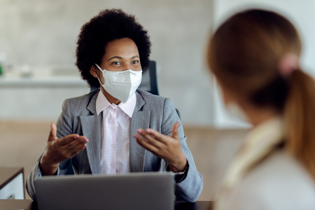 Black female mentor talking to her mentee during an in-person meeting wearing face masks.