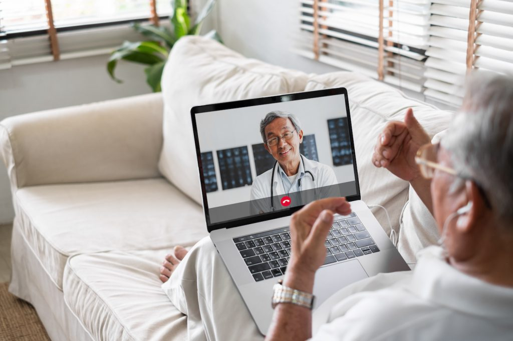 Man sitting on his couch for video call with doctor telemedicine telehealth concept