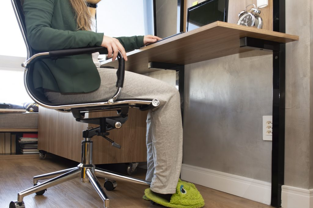 An image of a person sitting at a computer chair about to turn on their computer. They have long blonde hair and are wearing a green blazer, pyjama bottoms, and green frog slippers.